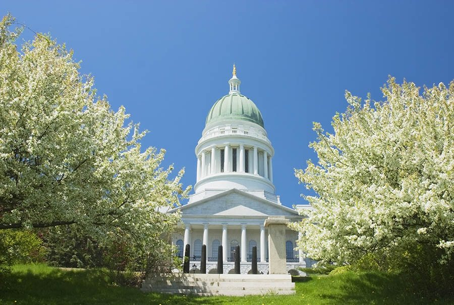 Maine capitol building with trees in foreground.