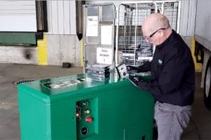 Employee feeds a hard drive into shredding machine
