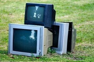 CRTs stacked on a grass lawn.