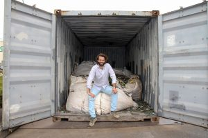 Closing the Loop founder Joost de Kluijver sits in a shipping container.