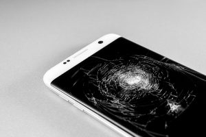Close up of a mobile device with a cracked screen.