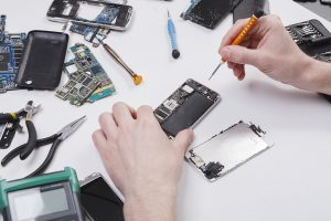 A worker repairs a mobile device.