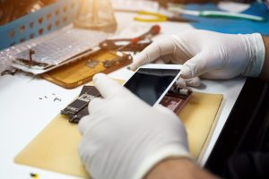 A technician works on repairing an iPhone.