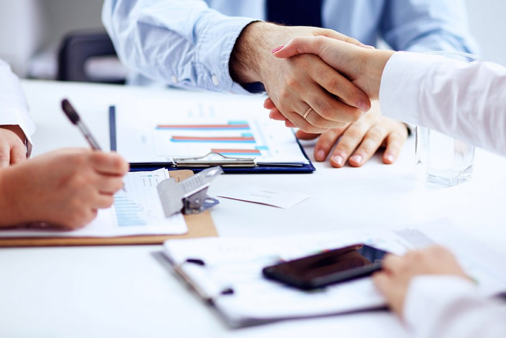 People shaking hands at a business meeting.