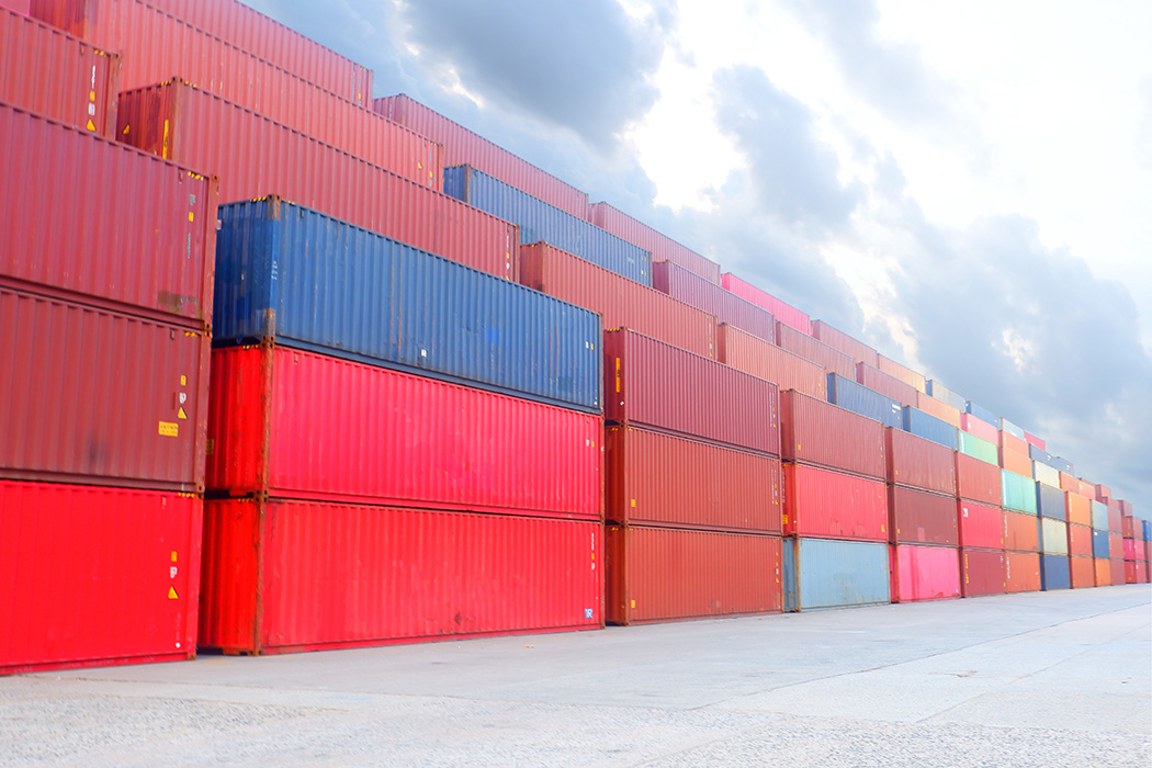 Stacked cargo shipping containers at port.