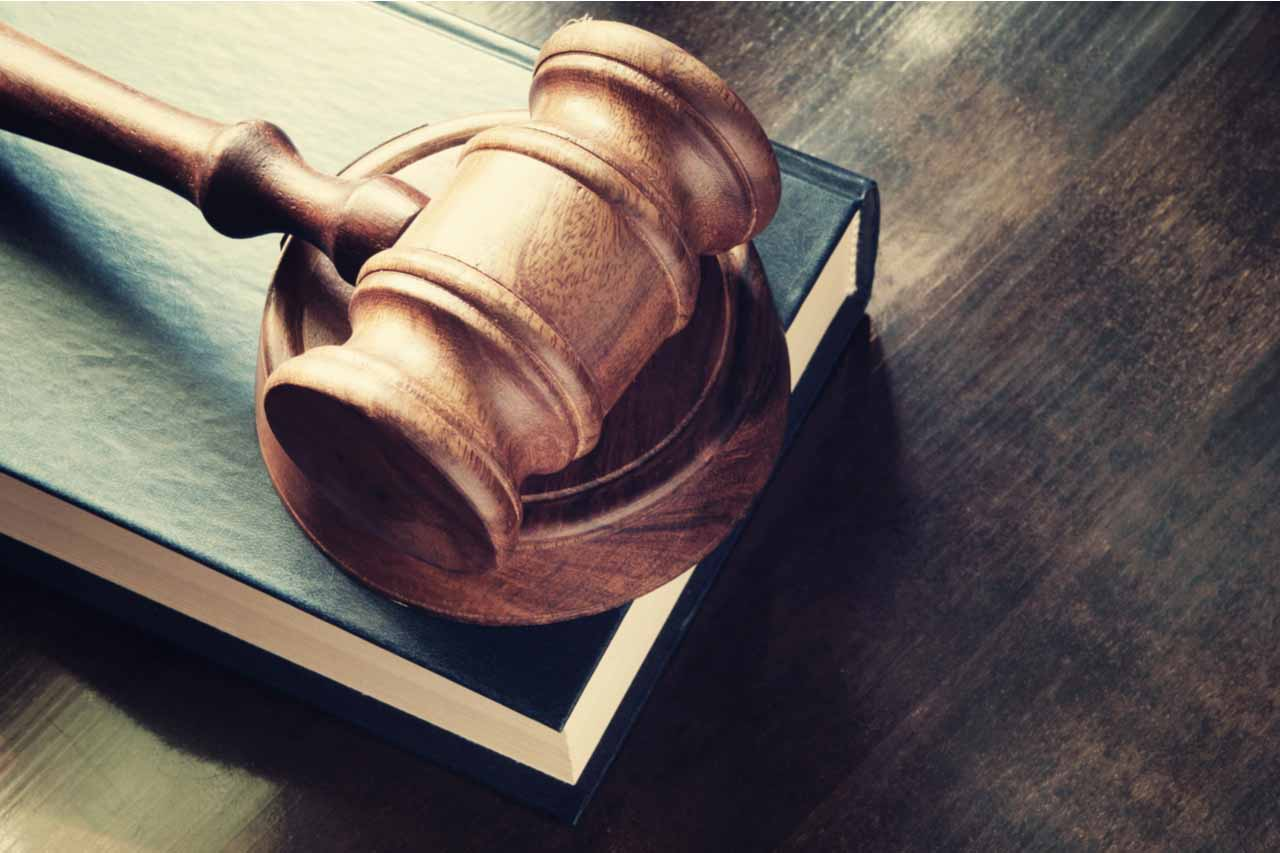 Gavel resting on a book on a desk.