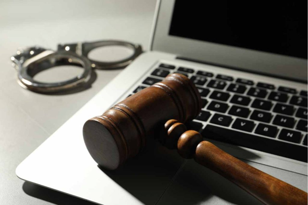Court gavel sitting on a laptop.
