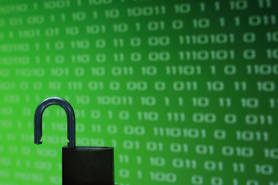 Open lock against a green binary code screen.