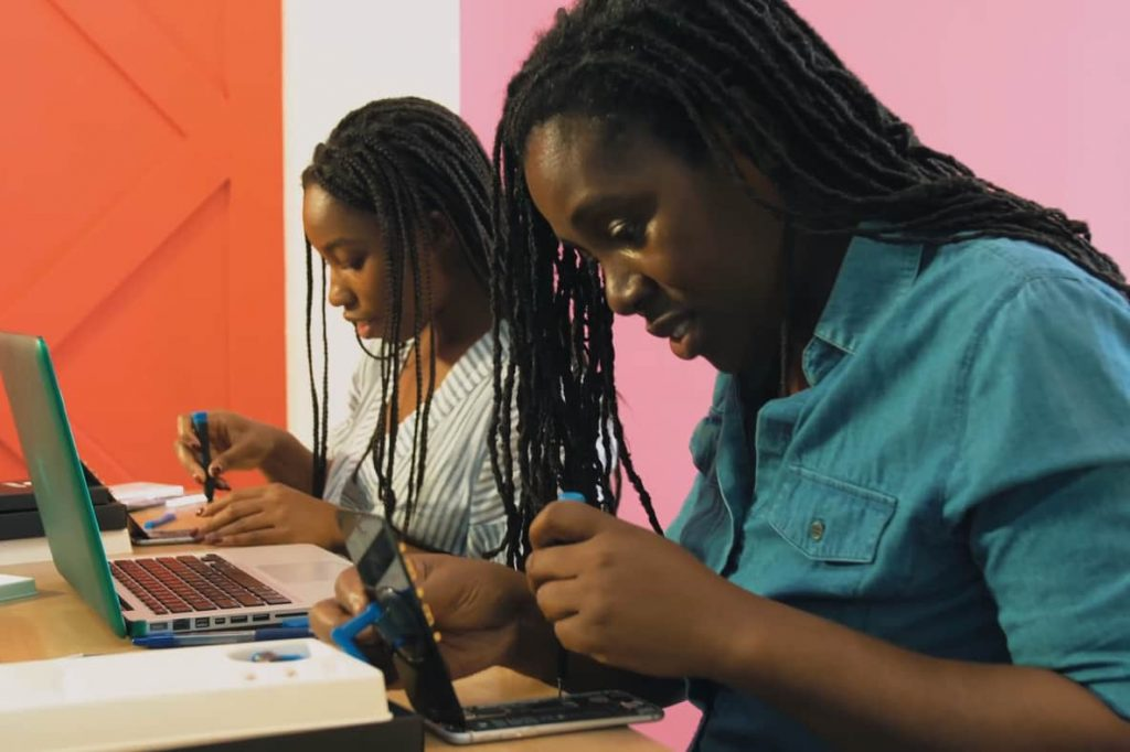 Two young women repairing their smartphones from the film Silicon Mountain