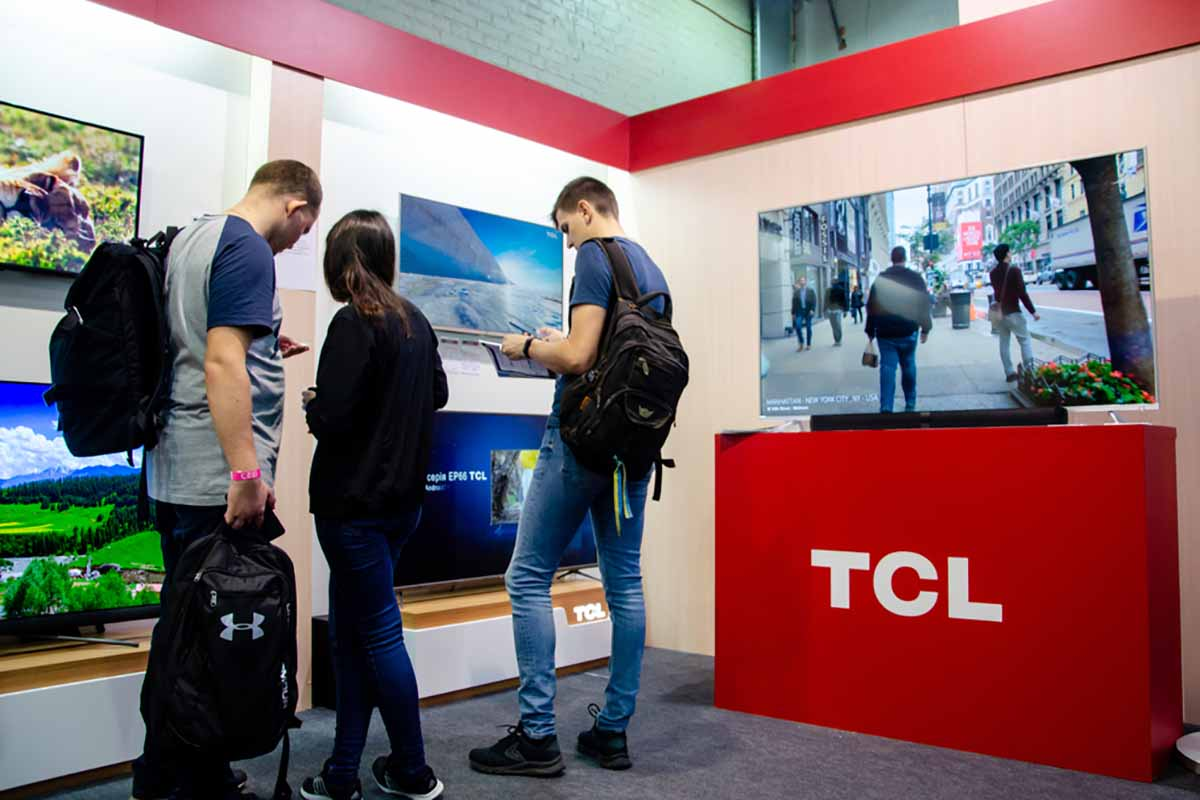 Shoppers in store looking at TCL televisions.