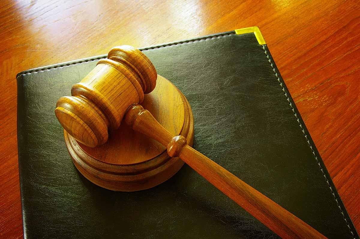 Court gavel rests on a leather binder on a desk.