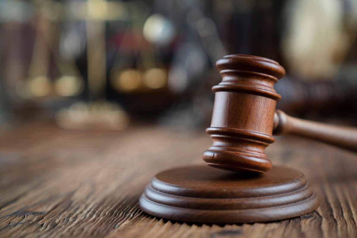 Court gavel resting on a wooden desk with blurred background.