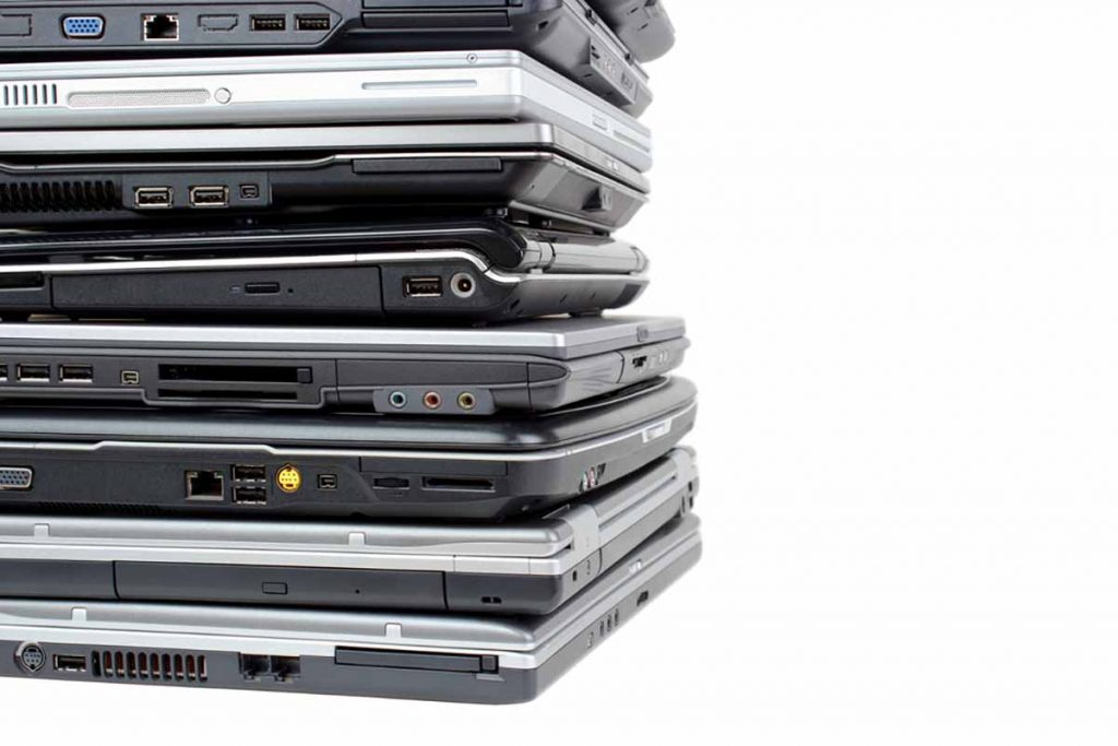 Stacked laptops for reuse and recycling against a white background.