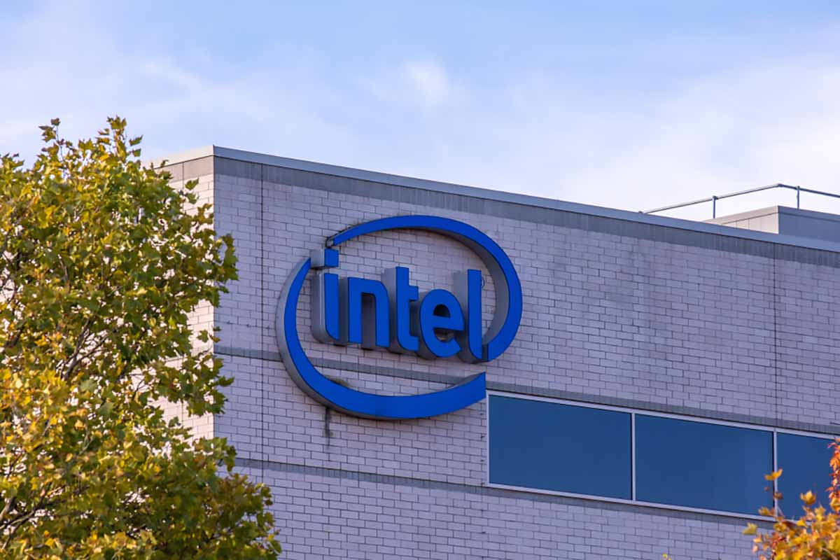 Intel sign on company building with blue sky and trees.