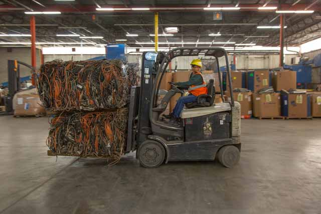 Employee driving forklift in the RecycleForce facility.