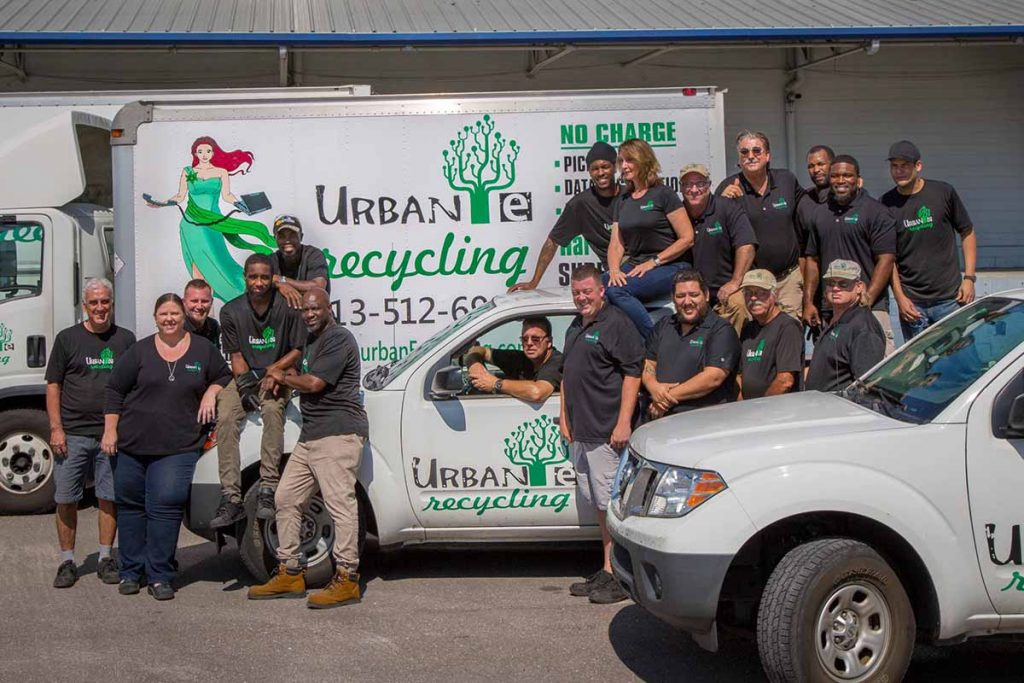 The Urban E Recycling team poses with company vehicles.