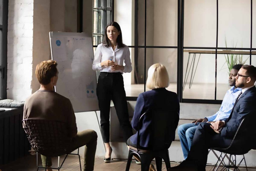 Business presentation by women in front of group.