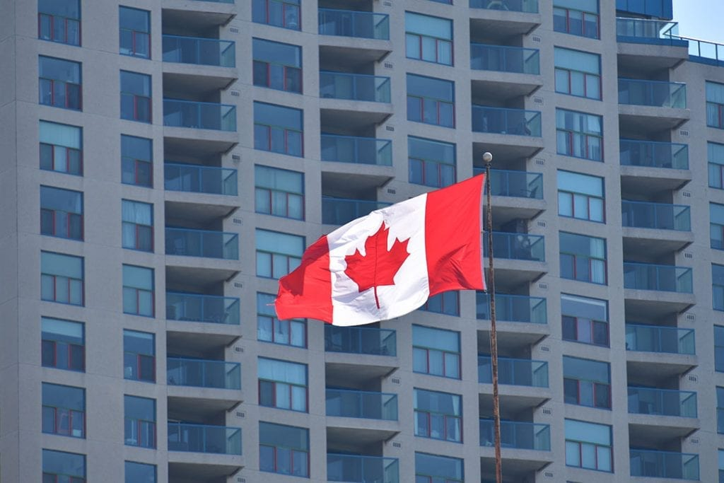 Canadian flag flying with building in background.