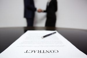 Contract with two people shaking hands in the background.