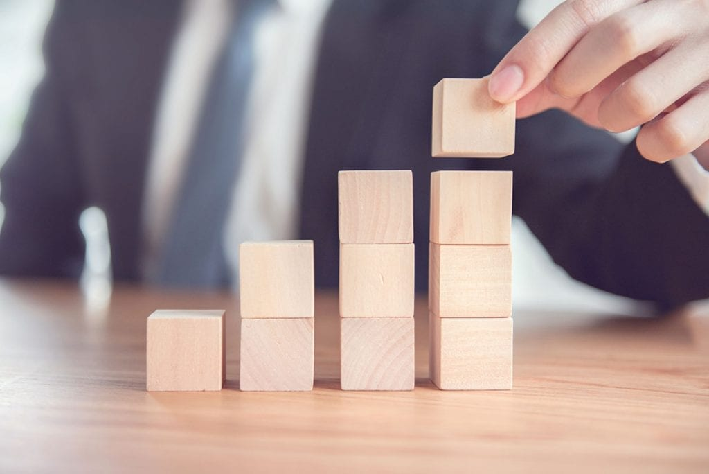 Person stacking blocks representing business growth.