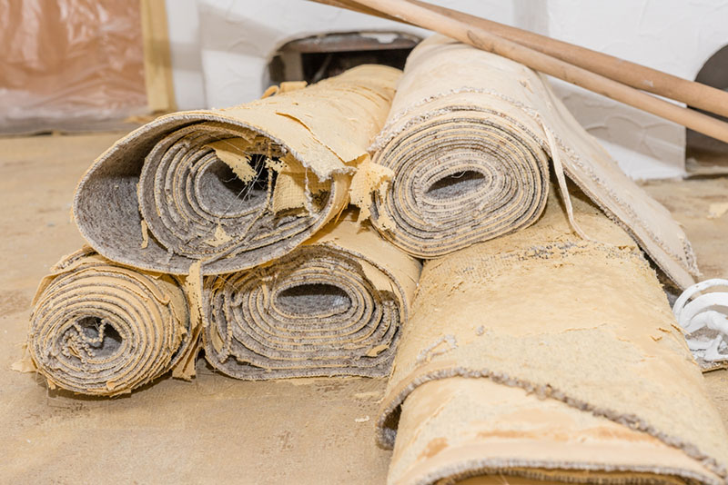 Old carpets rolled up for recycling.