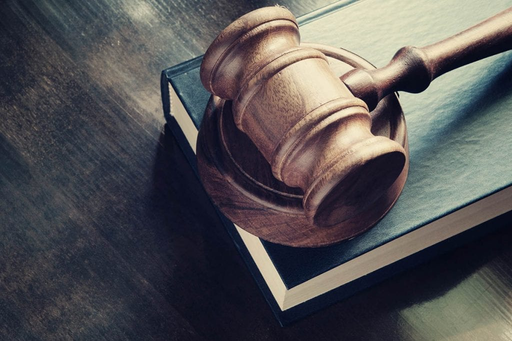 A gavel and a book on a table.