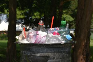 Plastic bottles and other materials in a public waste bin.