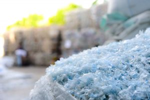 Plastic flake with baled plastic in background.