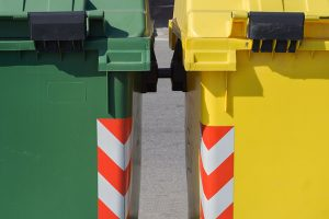 Close up of green and yellow waste and recycling bins.