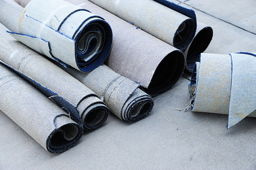 Old carpet pieces rolled up for recycling.