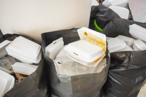 Garbage bags with foam food-service packaging.