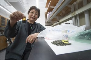 Purdue professor Linda Wang with oil product processed from polyolefins.