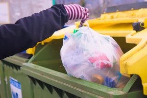 A person drops a bag of mixed plastics into a collection bin.
