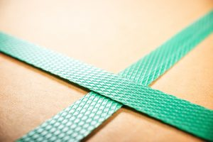 Close-up of green plastic strapping around a cardboard box.