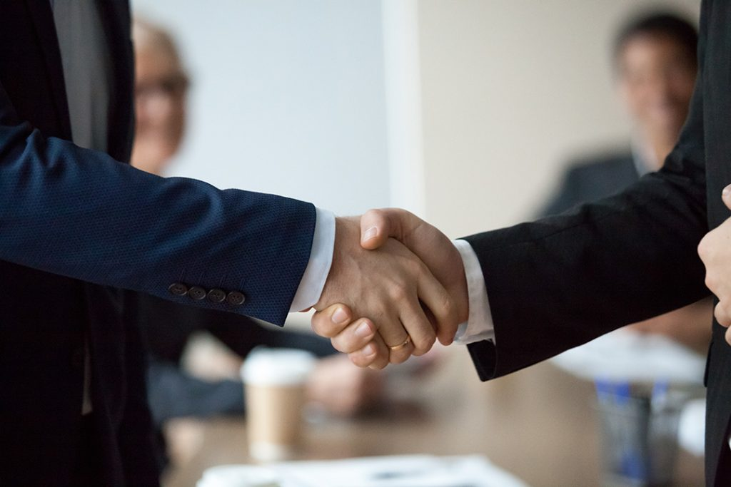 Two people in suits shake hands.