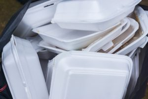 Many polystyrene takeout containers in a waste bin.