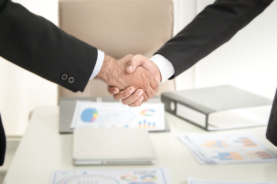 Business handshake with documents on conference table.