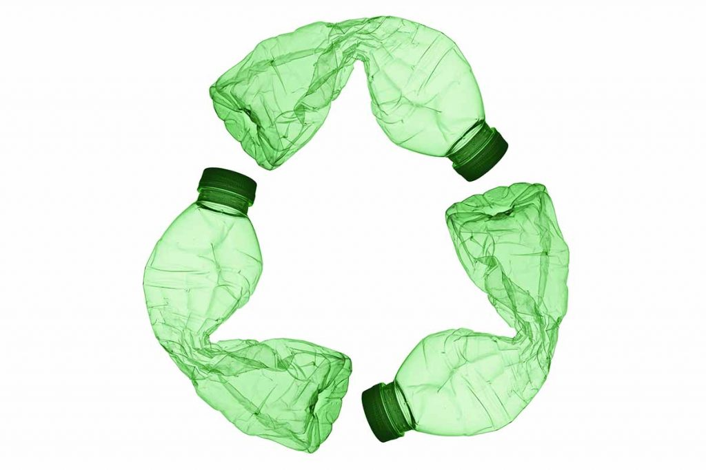 A recycle symbol made from three green plastic bottles.