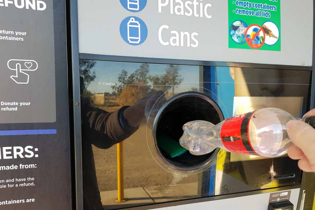 A person places a plastic bottle in a reverse vending machine.
