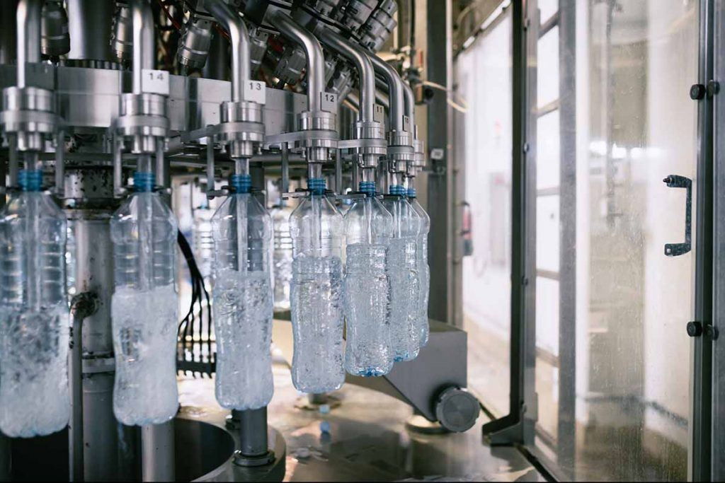 Plastic bottles being filled on a bottling line.