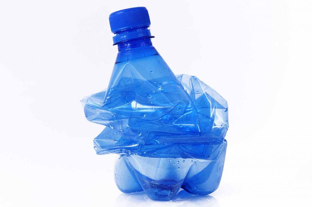 Squashed PET bottle on a white background.