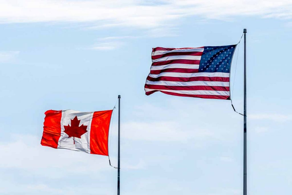 Canada and U.S. flags fly against a blue sky.