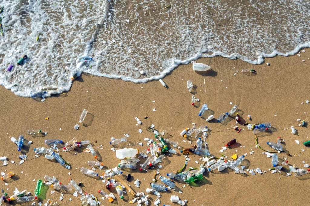 Plastics waste on a beach seen from above.