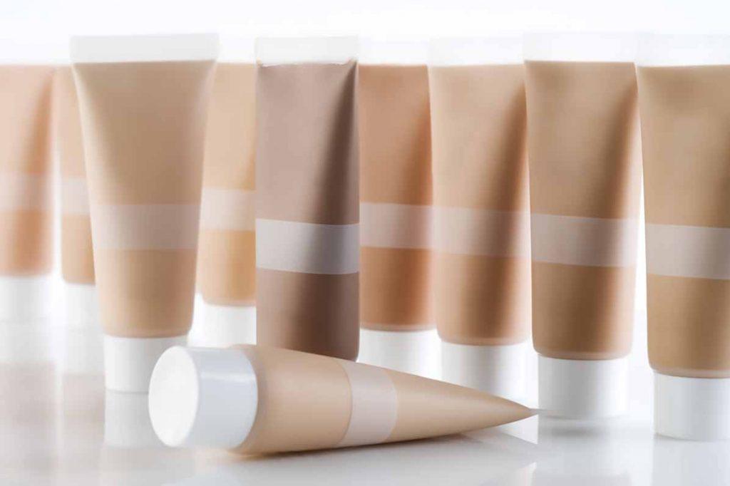 Many plastic cosmetic tubes against a white background.