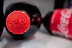 Bottles of Coca-Cola with focus on red cap with logo.