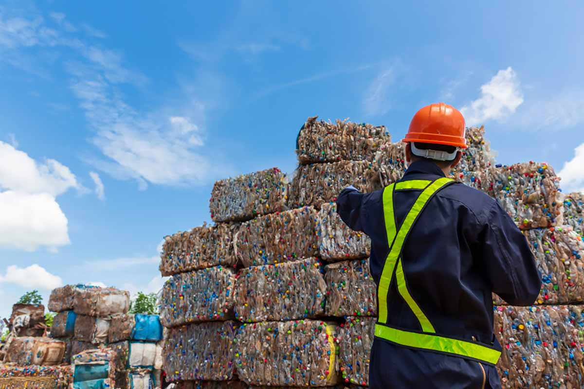 Recycling engineer in front of bales of material stacked outside.