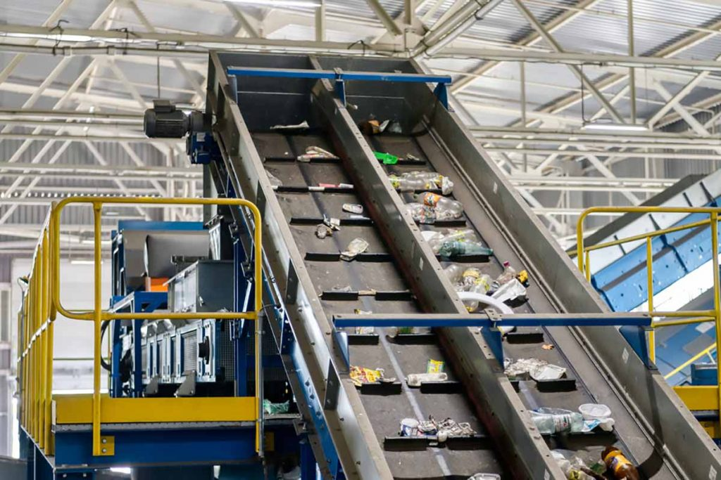 Material on a conveyor inside a sorting and processing facility.