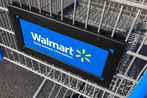 Walmart logo on shopping cart in store.