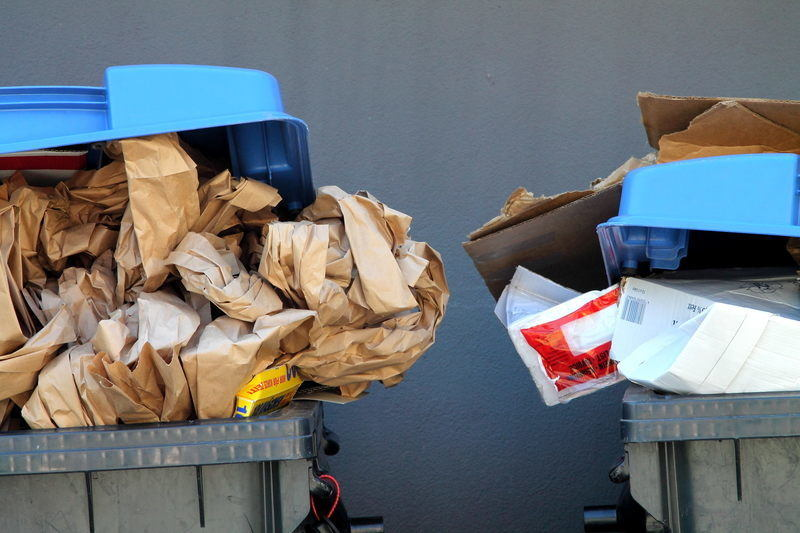 Recycling bins full with paper, cardboard and other materials.