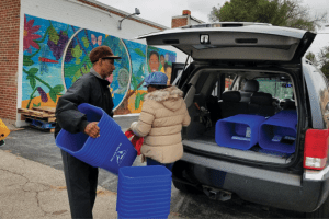 St. Louis residents unloading recycling bins from vehicle.